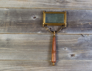 old rectangular shaped magnifying glass on rustic wood