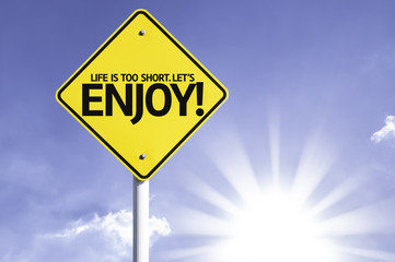 Life is Too Short. Let's Enjoy road sign with sun background