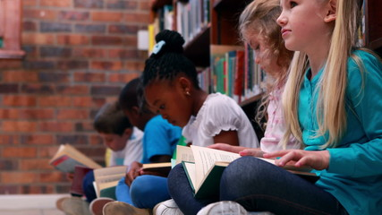 Pupils sitting in a row reading in the library