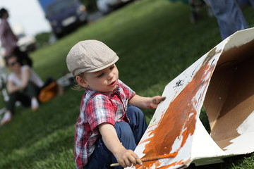 Child drawing picture on a cardboard