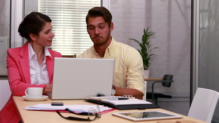 Casual business partners working together on laptop