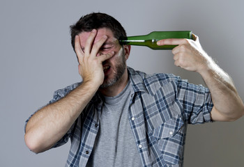 crazy man holding beer bottle as gun handgun pointing to head