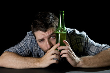 drunk man wasted at table with beer bottle looking funny