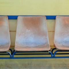 Old plastic seats on outdoor stadium players bench, worn chairs