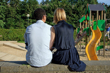 Couple in love sitting on the wall of a playground