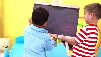Cute little boys wiping and knocking over mini chalkboard