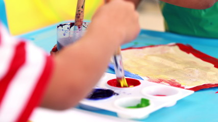 Cute little boys painting at table in classroom
