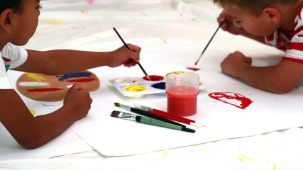 Cute little boys painting lying on paper