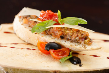 Italian appetizer bruschetta with tomato, basil and black olives