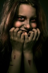 Girl possessed by a demon with a sinister smile