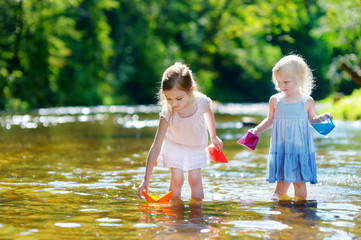 Two little sisters playing with paper boats