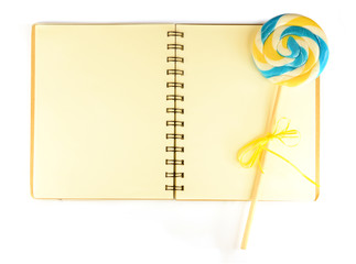 Notebook with pale lined paper and lollypop isolated on white ba