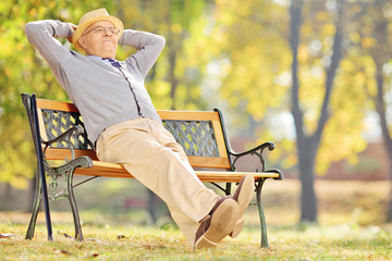 Senior gentleman sitting on bench and relaxing
