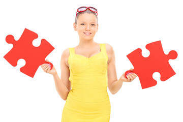 Trendy girl holding two pieces of puzzle