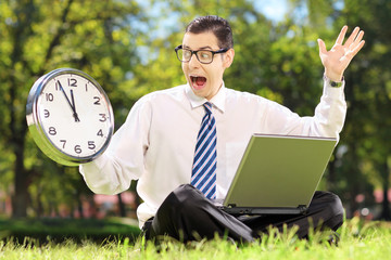 Young angry businessperson with computer sitting on grass and lo