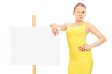 Young woman standing by a blank signboard