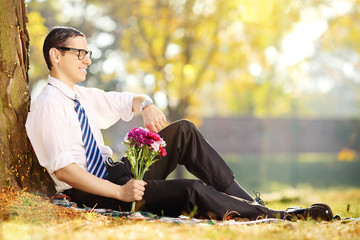 Young man with bunch of flowers sitting on a grass and checking