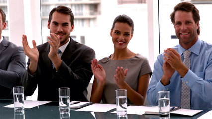 Business team applauding the camera at meeting