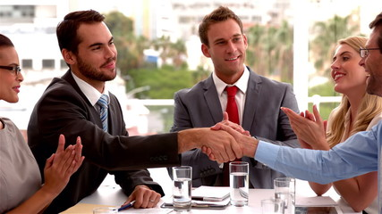 Business team applauding colleagues shaking hands