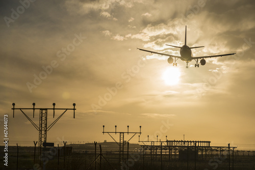 canvas print picture Airplane landing at dusk.