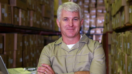 Warehouse worker smiling at camera with arms crossed