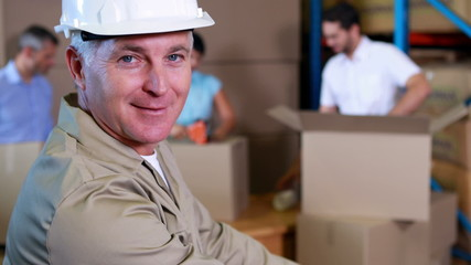 Warehouse worker stacking boxes and smiling at camera