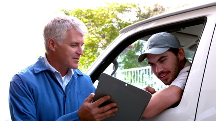 Delivery driver checking his list on clipboard with client