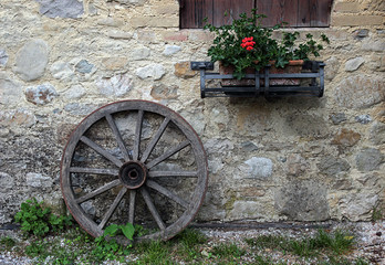 An old wooden wheel leaning against a stone wall