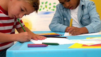 Cute little boys drawing at table in classroom