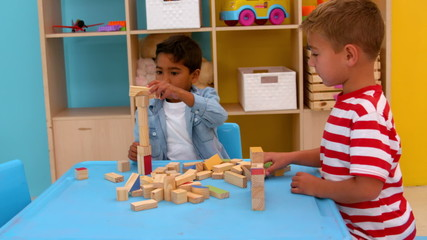 Cute little boys playing with building blocks at table in classr