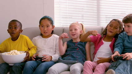 Cute little friends sitting on couch together playing video game