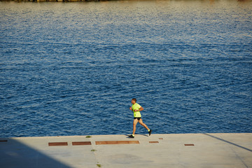 Male runner with muscular body running along the sea
