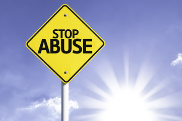 Stop Abuse road sign with sun background
