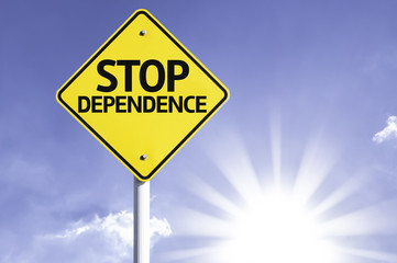 Stop Dependence road sign with sun background