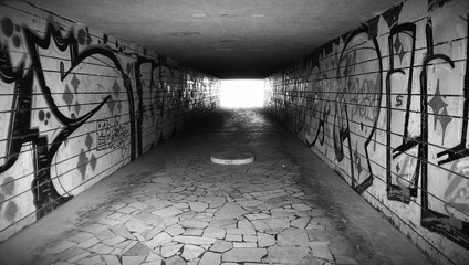 Dark underground pedestrian crossing tunnel with graffiti