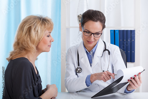 Doctor showing patient test results плакат