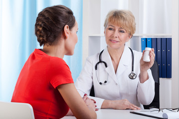 Mature Lady doctor showing patient medication