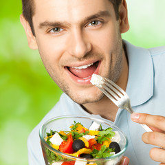 Portrait of young happy man eating salad