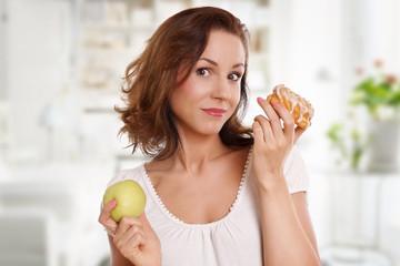 Junge Frau hat die Wahl zwischen Obst und Süßigkeiten