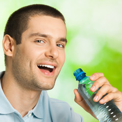 Young smiling man drinking water, outdoors