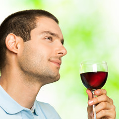 Young man with glass of redwine, outdoors
