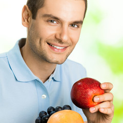 Portrait of young happy smiling man with plate of fruits, outdoo