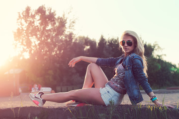Beautiful fashion young woman sunglasses sitting and posing at