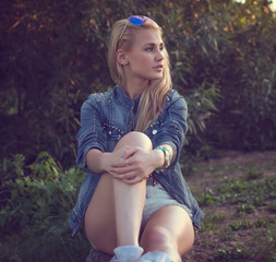 Sunny portrait of a beautiful fashion young girl sitting looking