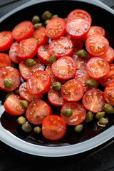 Sliced red cherry tomatoes with capers and sea salt, studio shot