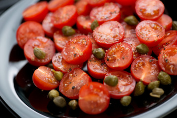 Glass plate with cherry tomatoes, capers, sea salt and pepper