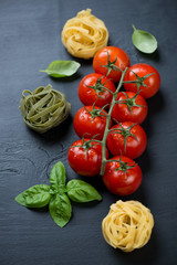 Branch of red tomatoes, raw colored tagliatelle and green basil