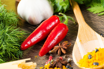chilli, herbs and spices lie on a wooden surface