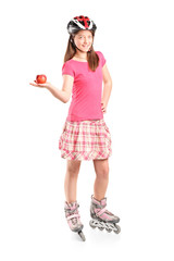 Young girl on roller skates holding an apple
