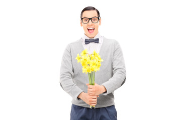 Excited young guy holding a bunch of flowers
